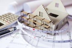 Neues Musterhaus auf Architekturplanplan am Schreibtisch Lizenzfreie Stockbilder