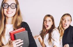 Neues Student bookwarm in den Gläsern gegen zufällige Gruppe auf weißem, jugendlich Drama Stockfoto