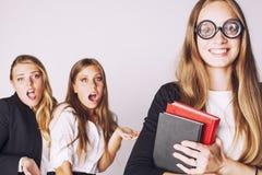 Neues Student bookwarm in den Gläsern gegen zufällige Gruppe auf weißem, jugendlich Drama Stockbild