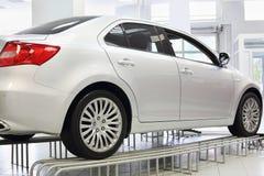 Neues weißes glänzendes Auto steht im hellen Büro des Shops Lizenzfreie Stockfotografie