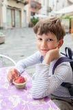 Neuf ans de garçon mangeant la crème glacée de baie Images stock