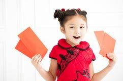 An neuf chinois petites filles tenant l'enveloppe rouge image stock