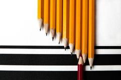 Neuf crayons jaunes et un rouges sur le papier structuré Images libres de droits