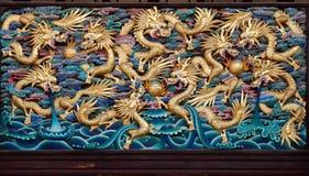 Neuf dragons d'or jouant avec des boules. En bois. Photographie stock