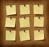 Neuf notes jaunes goupillées au fond grunge de liège Images stock
