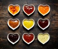 Neuf sauces et marinades colorées dans des cuvettes en forme de coeur Image stock
