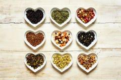 Neuf sortes colorées de thé dans des cuvettes en forme de coeur Image libre de droits