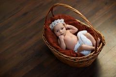 Neugeboren mit einer Krone im Korb auf Boden Lizenzfreies Stockfoto