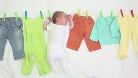Neugeboren und Baby kleidet auf einer Schnur, lustigen einem sauberen und einem trocken stock footage