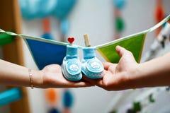 Neugeborene Babybeuten in den Elternhänden, Bauch der schwangeren Frau, blaue Schuhe, die an einer Schnur mit dekorativen Wäschek stockfotos