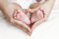 Neugeborene Babyfüße in den Mutterhänden Lizenzfreie Stockfotos