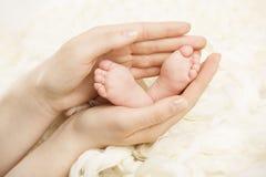 Neugeborene Babyfüße in den Mutterhänden Neugeboren und Elternteil Stockfoto