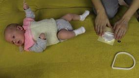 Neugeborene Babylüge auf Sofa- und Mutterhänden mischen spezielles Material stock footage