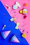 neugeborene Karte für Jungen Plätzchen in Form des Zubehörs für Kind, Parteihüte und Konfettis auf Draufsicht des rosa und blauen Stockfoto