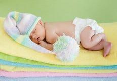 Neugeborene weared Schutzkappe, die auf bunten Tüchern schläft Stockbild