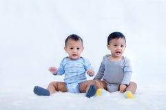 Neugeborene Zwillinge setzen sich hin Neugeborene Baby-Zwillinge setzen sich im Bett hin Reizend setzen Sie sich von den Neugebor stockbilder