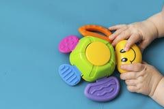 Neugeborener Griff des Kleinkindes kleine Handeine Spielzeugwanze mit einem L?cheln auf einem blauen Hintergrund aquamarin Nahauf lizenzfreies stockfoto