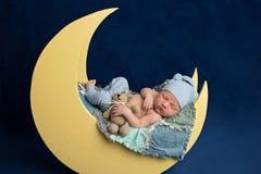 Neugeborener Junge, der auf dem Mond mit Teddy Bear schläft stockbild