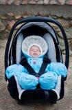 Neugeborener Junge, der im Autositz schläft Lizenzfreie Stockfotografie