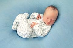 Neugeborener Junge schlafend auf einem blauen Hintergrund in den weißen Pyjamas mit a Lizenzfreie Stockfotografie