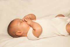 Neugeborenes asiatisches Baby, das auf einem Bett liegt Stockfotos
