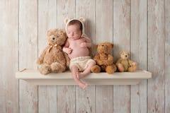 Neugeborenes Baby auf einem Regal mit Teddy Bears Stockfoto