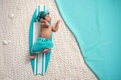 Neugeborenes Baby auf Surfbrett Lizenzfreies Stockfoto