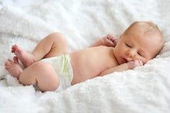 Neugeborenes Baby, das auf flaumige weiße Decke legt Stockbilder