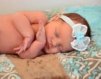 Neugeborenes Baby, das auf ihrer blauen Vliesdecke schläft Stockfotografie