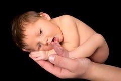 Neugeborenes Baby, das auf Zehe saugt Stockfotografie