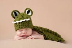 Neugeborenes Baby, das ein Alligatorkostüm trägt Lizenzfreies Stockbild
