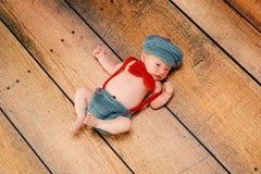 Neugeborenes Baby, das ein kleines Mann-Kostüm trägt Stockfotos