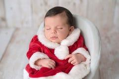 Neugeborenes Baby, das eine Frau trägt Klausel-Kleid stockbild
