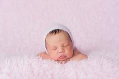 Neugeborenes Baby, das eine Rosa gestrickte Mütze trägt lizenzfreie stockbilder