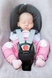 Neugeborenes Baby, das in einem Autositz sitzt Lizenzfreie Stockbilder