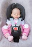 Neugeborenes Baby, das in einem Autositz sitzt Stockbild