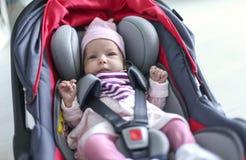 Neugeborenes Baby, das in einem Autositz sitzt Stockbilder