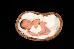 Neugeborenes Baby, das in einem hölzernen Korb schläft Lizenzfreie Stockbilder