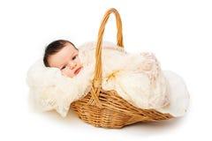 Neugeborenes Baby, das in einem Weidenkorb lächelt Stockbild