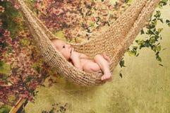Neugeborenes Baby, das in einer Hängematte sich entspannt Lizenzfreies Stockbild
