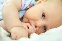 Neugeborenes Baby, das ihren Daumen saugend niederlegt Lizenzfreie Stockbilder
