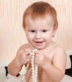 Neugeborenes Baby, das im Bett mit einer Perlenhalskette liegt Stockfotos