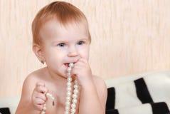 Neugeborenes Baby, das im Bett mit einer Perlenhalskette liegt Stockbild
