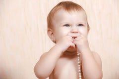 Neugeborenes Baby, das im Bett mit einer Perlenhalskette liegt Stockfoto
