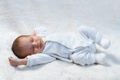Neugeborenes Baby, das im Sonnenlicht auf weißem Pelz schläft Stockbilder