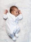 Neugeborenes Baby, das im Sonnenlicht auf weißem Pelz schläft Lizenzfreie Stockfotografie