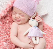 Neugeborenes Baby, das mit einem Spielzeughasen schläft Stockfotos