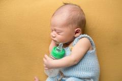 Neugeborenes Baby, das mit Flasche schläft Lizenzfreie Stockfotos