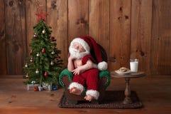 Neugeborenes Baby, das Santa Suit mit Bart trägt Stockfotografie