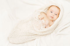 Neugeborenes Baby, das weiche woolen Decke, weißen Hintergrund bedeckt Lizenzfreie Stockbilder